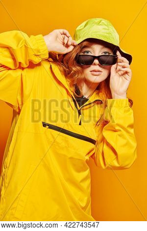 Portrait of a stylish teenage girl in yellow hoodie and sunglasses poses at studio on a yellow background. Youth style. Modern hip-hop dancer.