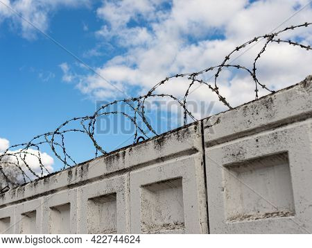 Concrete Fence With Barbed Wire On A Blue Sky Background