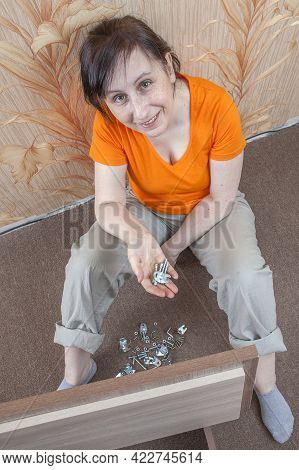Diy Assembly Of Furniture Flat Pack At Home. Mature European Woman Holding Fasteners In Palm Of Her