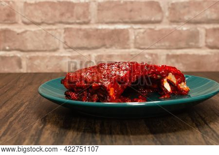 Ribs Prepared In The Oven With Barbecue Sauce. Roasted Ribs Served On Plate On Wooden Table.