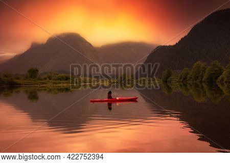 Adventure Caucasian Adult Woman Kayaking In Red Kayak Surrounded By Canadian Mountain Landscape. Sun