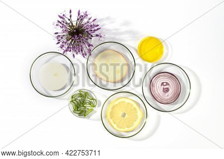 Laboratory Petri Dishes With Onions, Oil, Lemon, Aloe Vera And Onion Flower Head Isolated On White B