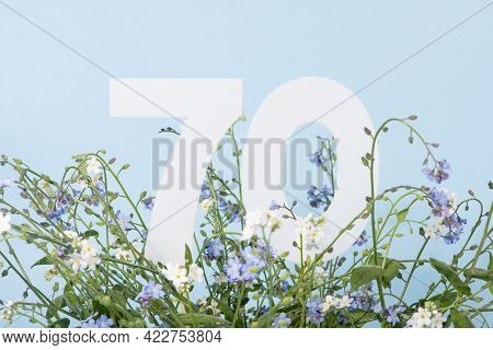 Number Seventy Among Blue Forget-me-not Flowers.  Birthday, Anniversary, Jubilee Concept. For Invita