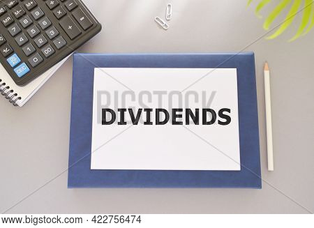 Text Dividends Written In Notebook, Gray Background, Pencil, Calculator, Finance Concept