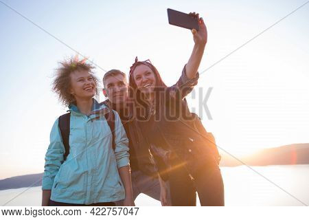Group Of Friends Resting On Mountain While Hiking. Hikers Relaxing And Taking Selfie. Friends Taking