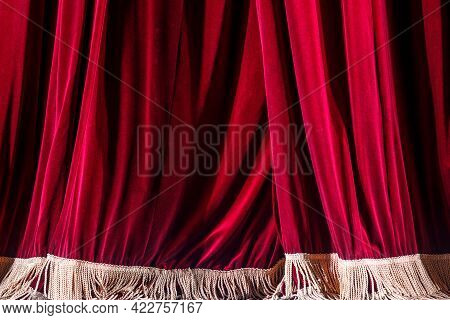 Fragment Of A Red Curtain On A Theater Stage, Illuminated By Floodlights. Intermission Between Perfo