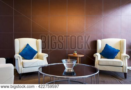 Cream Armchair And Blue Cushion In Front Of A Brown Leather Panel. A Glass Bowl With Water Placed On