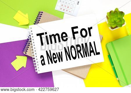Time For A Nbew Normal. Notepad On A Colorful Background. White Purple And Yellow Background.
