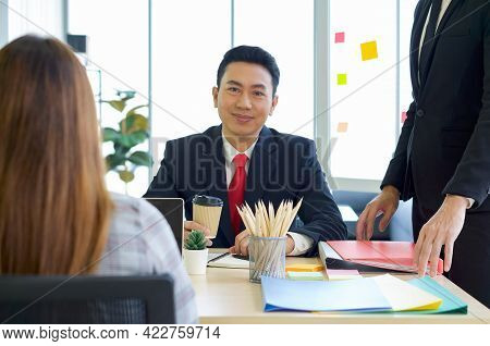 Business Executives Team Meeting In Modern Office With Laptop Computer, Coffee And Document On Table