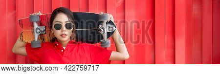 Young Asian Woman In Red T-shirt With Collar Holding The Surfskates Board In Shoulder Position In Fr