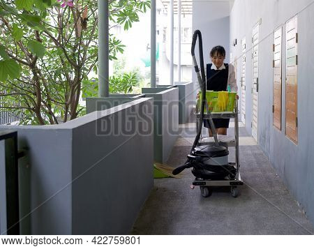 Young Hotel Maid In Blue Uniform Push Housekeeping Cart On The Corridor In Front Of The Hotel Room.