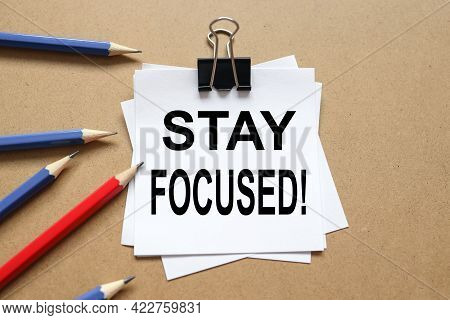 Stay Focused. Text On The Sticker. Paper Is Clamped With A Paper Clip. Paper On A Wooden Background