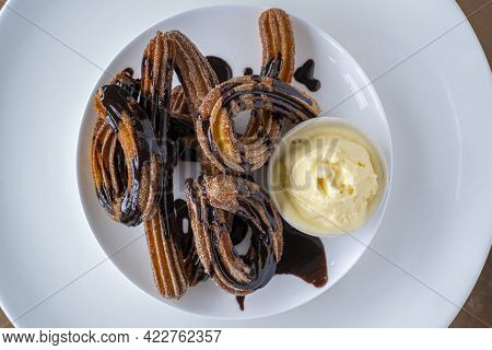 Sweet Churros With Chocolate And Vanilla Ice Cream On White Plate