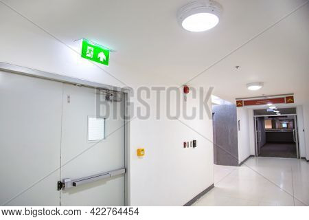 Close Up The Green Emergency Fire Exit Sign Or Fire Escape With The Doorway Or Door Exit In The Buil