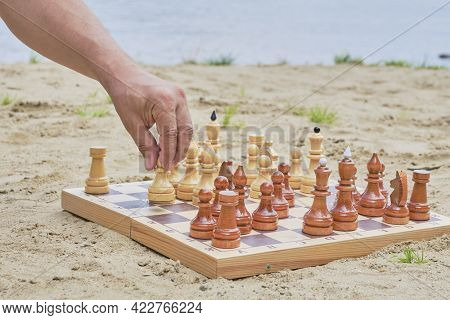The Hand Of A Senior Man Holding A Pawn For A Move In A Chess Game On The Background Of A Sandy Beac