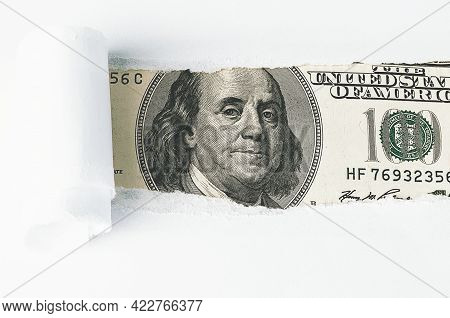 The Face Of Benjamin Franklin On A Hundred-dollar Bill, From A Torn Window In White Paper. Backgroun