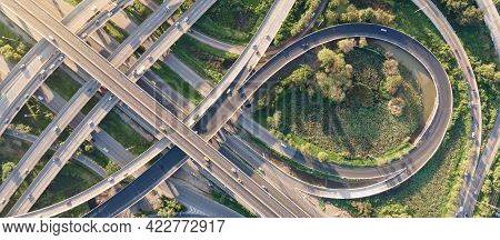 Aerial View Of Road Interchange Or Highway Intersection With Busy Urban Traffic Speeding On The Road