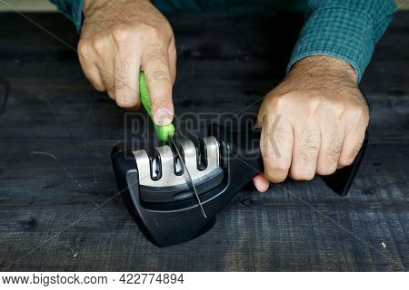 Close Up Photo Of Someone's Hand Sharpening A Kitchen Knife Using A Sharpener