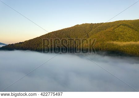 Aerial View Of Vibrant Sunrise Over White Dense Fog With Distant Dark Silhouettes Of Mountain Hills