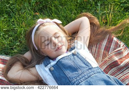 Pretty Little Child Girl Laying Down On Green Grass In Summer Taking A Nap.