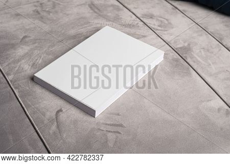 Book With Blank Cover On Gray Velvet Sofa Backdrop, Editable Mock-up Series Template Ready For Your