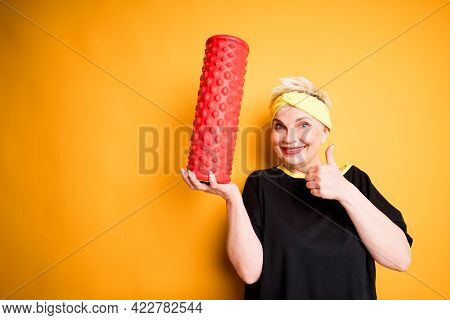 Cheerful Elderly Woman In A Black T-shirt Holds Fascia In Her Hand And Raises Her Thumb Up Smiling