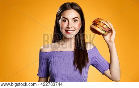 Takeaway Food Delivery Concept. Happy Girl Holding Hamburger And Smiling. Hungry Young Woman Eating