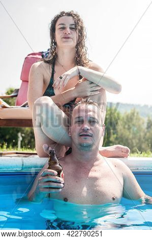 Happy Lovers On Honeymoon Travel. Young Couple In Swimming Pool. Relationship, Romance, Love. Summer