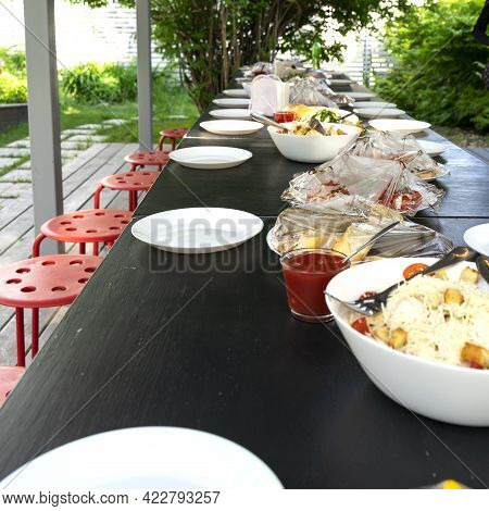 Preparation Of An Outdoor Banquet Table By The Catering Service. Food Covered With Plastic