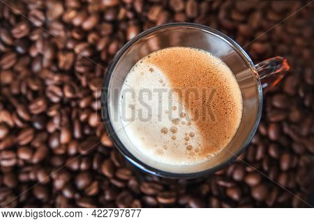 Cup Of Cappuccino With Froth Top View Close-up. Defocus From Coffee Beans And Copy Space.
