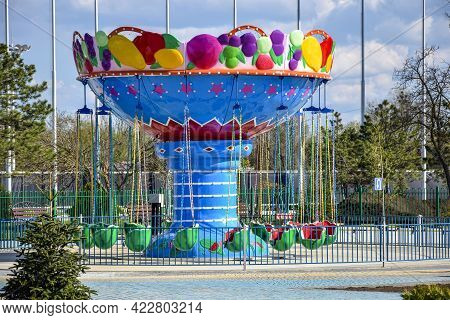 Children's Attraction Is Quarantined Due To Covid-19. Colorful Carousel On Blue Sky Background. Clos