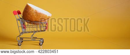 A Piece Of Bread Is In A Supermarket Trolley. Yellow Background. The Concept Of Economic Crisis, Sho