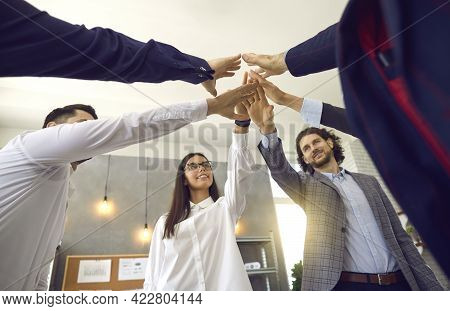 Diverse Business Team Joining Hands Together Standing In Office View From Bottom