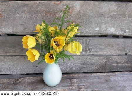 A Large Bouquet Of Bright Yellow Tulips With Green Leaves In A White Vase. The Background Is Rough O