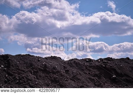 Artificial Mound Of Mountain Rubble On The Background Of A Blue Sky With Clouds. Background.