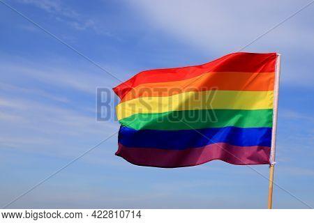 Waving Gay Pride Rainbow Flag In Blue Summer Sky. Bright Flag Of The Lgbt Community For Lesbian, Gay