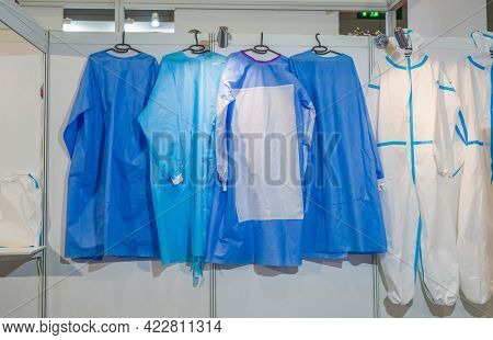 collection of medical protective gowns hang on a hanger in a hospital, prevention COVID-19, medical clothing for a doctor