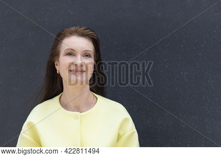 Portrait Happy  Adult Businesswoman, Smiling Kind Middle Aged Woman. Mature Lady At Grey Background.