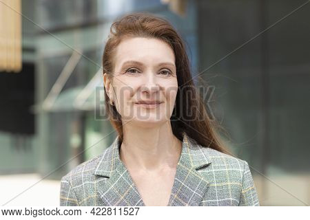 Portrait Happy Kind Adult Smiling Woman. Mature Middle Age Lady With Long Brunette Hair With Smile.
