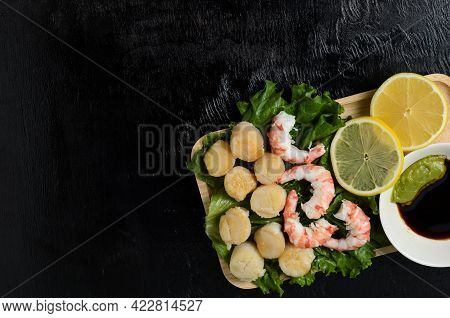 Fried Scallop With Boiled Shrimp Tail On A Salad Leaf With Lemon, Soy Sauce And Wasabi On A Dark Bac