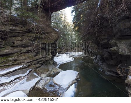 Winter Frozen Stream Flowing Under The Small Bridge In Natural Stone Arch In Deep Valley. Carpathian