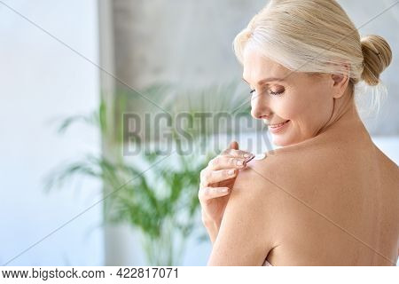 Back View Of Naked Gorgeous Middle Aged 50s Woman Applying Moisturizing Body Lotion After Shower. Ad