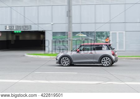 Moscow, Russia - June 2021: Mini Cooper Is Accelerating In City Road On Urban Background