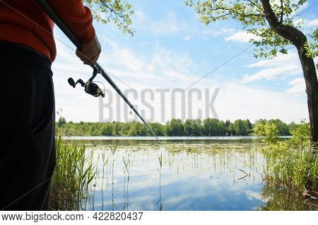 Fishing On The Lake. Fisherman Holding A Fishing Rod Outdoors Close-up. Fishing On A Wild Lake Durin