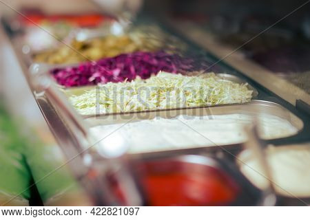Sauces And Cut Vegetables And Lettuce In A Showcase Window Of A Fast-food Restaurant