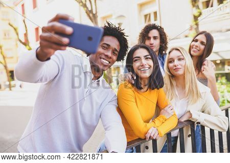 Multi-ethnic Group Of Friends Taking A Selfie In The Street With A Smartphone.