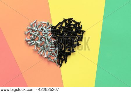 Heart Of Two Opposite Halves On A Rainbow Background, Valentine's Card Made Of Screws On Colored Pap