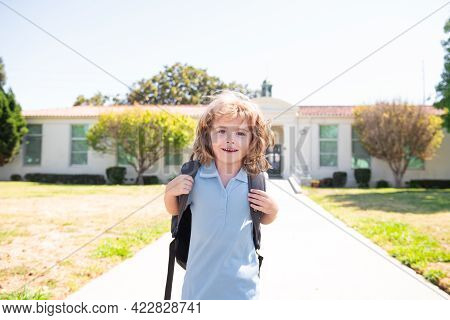 Happy Smiling Kid Is Going To School. Child Boy With Bag Go To Elementary School. Primary School. Pu