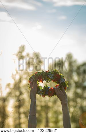 Hands With A Wreath Of Midsummer Flowers Against The Sunset. Old Latvian Culture Tradition Ligo. Mid