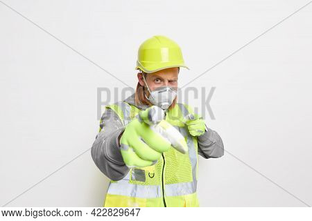Serious Self Confident Male Builder Points Directly At Camera Wears Helmet Respirator And Safety Uni